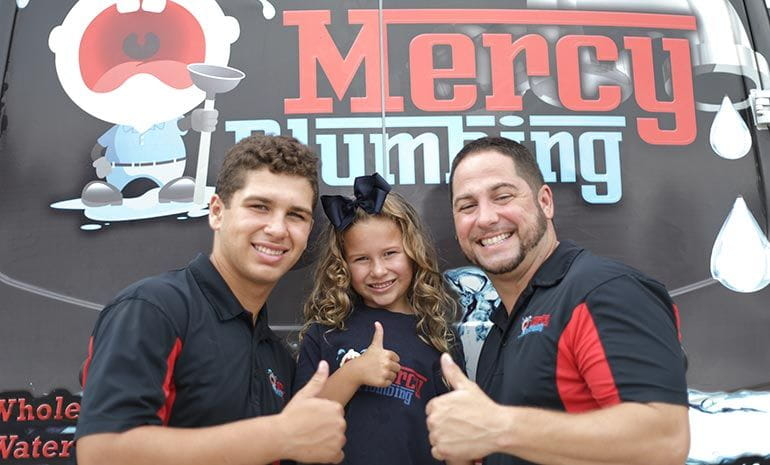 Mercy Plumbing technicians with a young girl in middle